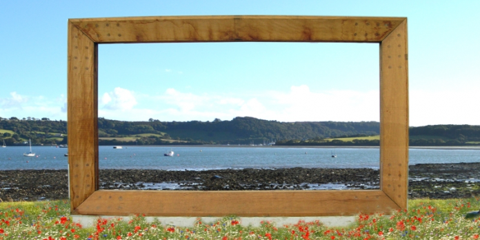 A large wooden frame surrounded by grass and flowers, overlooking boats in a bay